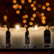 Burning candle with christmas tree bokeh — Stock Photo #38393771