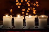 Burning candle with christmas tree bokeh — Zdjęcie stockowe