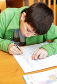 Bored and tired boy doing homework — Stock Photo