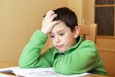 Garçon s'ennui et fatigué à faire leurs devoirs — Photo