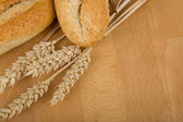 Roll on wooden table with ears of wheat grain — Stock Photo