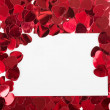 Small red confetti and big hearts on white background — Stock Photo