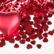 Small red confetti and big hearts on white background — Stockfoto