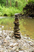 Stones pyramid near small river — Stock Photo