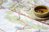 Old touristic compass on map — Stock Photo