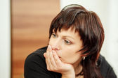 Tired woman holding head, looking out — Stock Photo