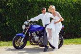 Beautiful young wedding couple on motorcycle — Stock Photo