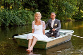 Young just married bride and groom on boat — Stock Photo