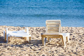Two old sunloungers on tunisian beach — Stock Photo