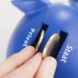Putting coins into piggy bank - Stock Photo
