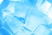 Bakgrund med isbitar i blått ljus — Stockfoto