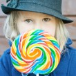 Rainbow lollypop and girl — Stock Photo