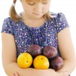 Girl holding plums on the isolated background — Lizenzfreies Foto