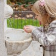 A girl drinking from fountain — Stockfoto