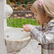 A girl drinking from fountain — Foto de Stock