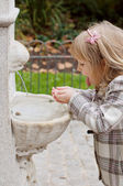 A girl drinking from fountain — Stock Photo