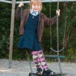 Foto Stock: Girl in school uniform on swing