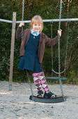 Girl in school uniform on a swing — Stock Photo
