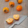 Cut persimmon fruit and knife — Stock Photo