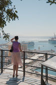 Lady watching the ships in a harbour — Stock Photo