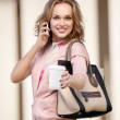 Woman on phone offering cup of coffee. — Stock Photo