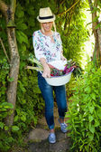 Woman carrying a bucket with vegetables — Stock Photo