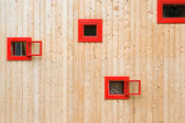 Open red windows on a wooden wall — Stock Photo