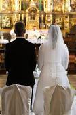Newlyweds at the catholic church — Stock Photo