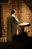 Priest reading the Holly Bible in an old church — Stock Photo
