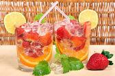 Bebida cor de laranja, morango, limão e gelo — Fotografia Stock