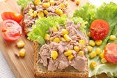 Sandwich with tuna and corn on wood background — Stock Photo