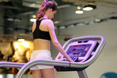 Young girl exercising on treadmill at a gym — Stock Photo