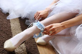 Young bride putting on blue garter sitting on the couch — Stock Photo
