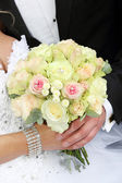 Newlyweds with wedding rose bouquet after wedding ceremony — Stock Photo
