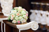 Bridal wedding bouquet lying on the hassock during the marriage  — Stock Photo