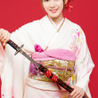 Beautiful kimono woman on red background — Stock Photo