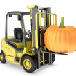 Yellow fork lift truck lifts orange pupmkin — Stock Photo