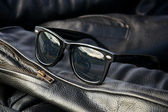 Leather jacket detail with sunglasses — Stock Photo