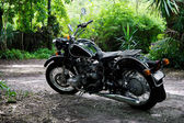 Vintage black motorcycle in subtropical setting — Stock Photo