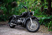 Vintage black motorcycle in tropical setting — Stock Photo