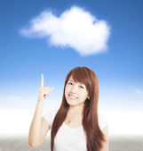 Smiling young woman pointing to the cloud — Stock Photo