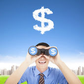 Happy businessman holding binoculars and watching the money clou — Stock Photo