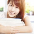 Smiling student holding books in the classroom — Stock Photo #12383435
