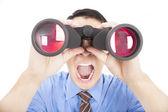Surprised businessman looks through binoculars and isolated — Stock Photo