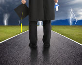 Graduate standing on the road and watching the storm — Stock Photo