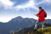 Young man touching the tablet pc on the top of mountain — Stock Photo