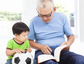 Grandfather reading a story book for his grandson — Stock Photo