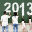 Stock Photo: Happy family drawing 2013 on the chalkboard