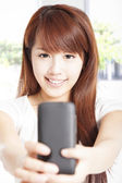 Beautiful young woman holding and watching smart phone — Stock Photo