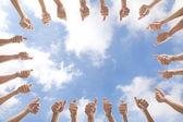 Grupo de con los pulgares para arriba en el fondo de la nube — Foto de Stock